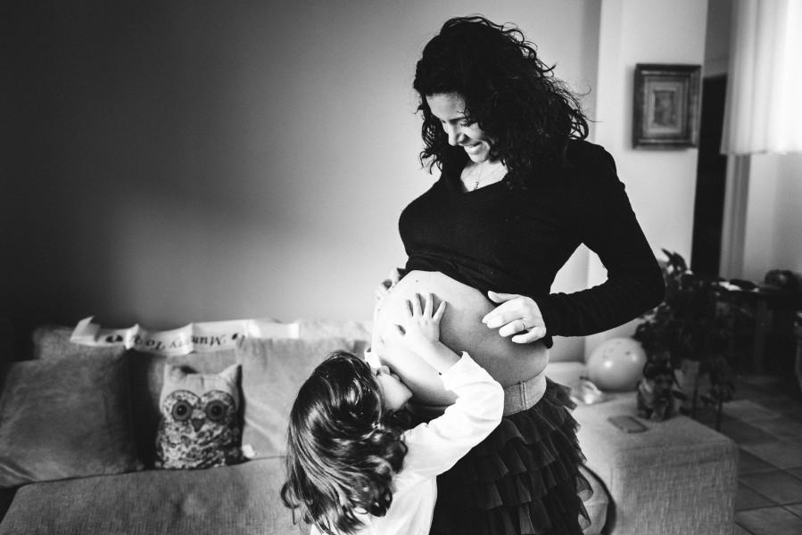foto di bambina che bacia pancia mamma